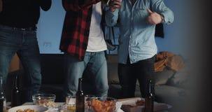 Τρεις φίλοι που προσέχουν τον αγώνα ποδοσφαίρου στη TV στο σπίτι, ενθαρρυντική καλύτερη ομάδα ποδοσφαίρου Συγκίνηση Οι θαυμαστές  απόθεμα βίντεο