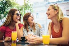 Τρεις φίλοι σε έναν καφέ που έχει τη διασκέδαση Στοκ Φωτογραφίες
