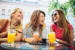 Τρεις φίλοι σε έναν καφέ που έχει τη διασκέδαση Στοκ φωτογραφία με δικαίωμα ελεύθερης χρήσης