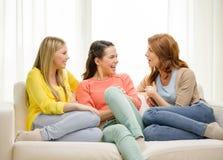 Τρεις φίλες που διοργανώνουν μια συζήτηση στο σπίτι στοκ φωτογραφίες