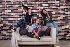 Τρεις φίλες που κάθονται στον καναπέ και το χαμόγελο Στοκ Εικόνα