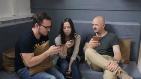Τρεις φίλοι κάθονται στον καναπέ στο στούντιο και παίζουν με τα smartphones απόθεμα βίντεο