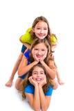 Τρεις φίλοι κοριτσιών παιδιών ευτυχείς που συσσωρεύει σε μια σειρά Στοκ φωτογραφίες με δικαίωμα ελεύθερης χρήσης