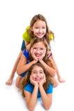 Τρεις φίλοι κοριτσιών παιδιών ευτυχείς που συσσωρεύει σε μια σειρά Στοκ εικόνες με δικαίωμα ελεύθερης χρήσης