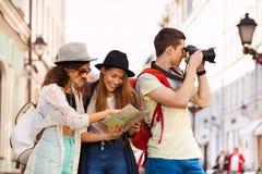 Τρεις φίλοι μαζί με το χάρτη και τη κάμερα πόλεων Στοκ Φωτογραφία