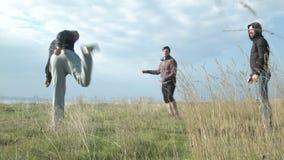 Τρεις φίλοι παίζουν τη σφαίρα, που γεμίζει τα πόδια τους αθλητισμός παιχνιδιών απόθεμα βίντεο