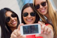 Τρεις φίλοι που παίρνουν τις φωτογραφίες με ένα smartphone Στοκ φωτογραφία με δικαίωμα ελεύθερης χρήσης