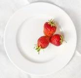 Τρεις φράουλες σε ένα άσπρο πιάτο Στοκ Εικόνες