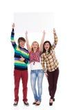 Τρεις φωνάζοντας νέοι με το έμβλημα Στοκ εικόνα με δικαίωμα ελεύθερης χρήσης