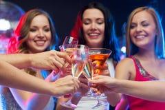 Τρεις χαμογελώντας γυναίκες με τα κοκτέιλ και τη σφαίρα disco Στοκ Φωτογραφίες
