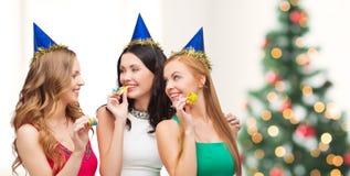 Τρεις χαμογελώντας γυναίκες στα καπέλα που φυσούν τα κέρατα εύνοιας Στοκ φωτογραφία με δικαίωμα ελεύθερης χρήσης