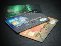 Τρεις χρωματισμένες πιστωτικές κάρτες που απομονώνονται στο μαύρο ξύλινο backgro γραφείων Στοκ Εικόνες