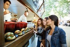 Τρεις όμορφες νέες γυναίκες που αγοράζουν τα κεφτή σε ένα φορτηγό τροφίμων Στοκ Εικόνα