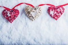 Τρεις όμορφες ρομαντικές εκλεκτής ποιότητας καρδιές κρεμούν σε μια κόκκινη ζώνη σε ένα άσπρο υπόβαθρο χιονιού Έννοια ημέρας βαλεν στοκ εικόνες