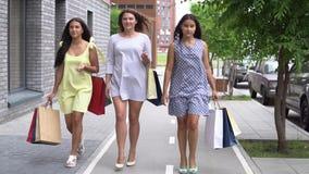 Τρεις όμορφες φίλες πηγαίνουν κατά μήκος της οδού με τις συσκευασίες μετά από να ψωνίσουν κίνηση αργή φιλμ μικρού μήκους