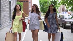 Τρεις όμορφες φίλες πηγαίνουν κατά μήκος της οδού με τις συσκευασίες μετά από να ψωνίσουν κίνηση αργή HD απόθεμα βίντεο