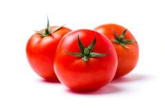 Τρεις ώριμες κόκκινες ντομάτες στο λευκό απομονώνουν το υπόβαθρο, κινηματογράφηση σε πρώτο πλάνο στοκ φωτογραφία
