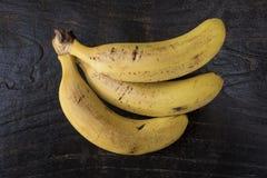 Τρεις ώριμες μπανάνες Cavendish με τους μικρούς μώλωπες που τοποθετούνται σε έναν ξύλινο καφετή πίνακα στοκ φωτογραφία