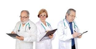 Τρεις ώριμοι γιατροί που συμπληρώνουν τις εκθέσεις Στοκ Φωτογραφίες