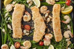 Τρεις fishfingers και γαρίδες με τις ντομάτες και τα κρεμμύδια κερασιών Στοκ φωτογραφία με δικαίωμα ελεύθερης χρήσης
