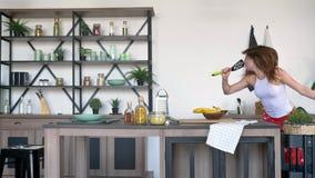 Τρελλή γυναίκα με την τρίχα πιπεροριζών που χορεύει, που τραγουδά spatula στην κουζίνα και που θέτει για τη κάμερα, εύθυμος και ε απόθεμα βίντεο