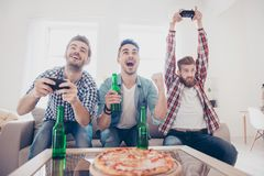 Τρελλός, διασκέδαση, χαρά, νικητές και χαλαρότερος! Οι νεαροί άνδρες κάθονται σε ομο στοκ φωτογραφία