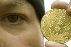 Τρελλός εραστής bitcoin με ένα χρυσό νόμισμα στο χέρι σας, αστείος ανθρακωρύχος με BTC κοντά στο πρόσωπο στοκ φωτογραφία με δικαίωμα ελεύθερης χρήσης