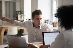 Τρελλός υπάλληλος ανδρών που κατηγορούν το συνάδελφο γυναικών για το λάθος στοκ εικόνα με δικαίωμα ελεύθερης χρήσης
