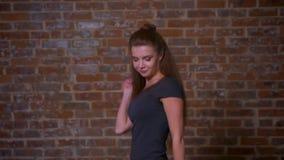 Τρελλό ευτυχές μήκος σε πόδηα χορού της καυκάσιας γυναίκας πιπεροριζών στο στούντιο τούβλου, το περιστασιακό ύφος και τις αστείες απόθεμα βίντεο
