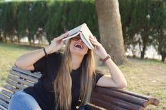Τρελλό ξανθό κορίτσι με τα γυαλιά που κρατά ένα βιβλίο στο κεφάλι στοκ εικόνες με δικαίωμα ελεύθερης χρήσης