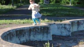 Τρεξίματα λίγων όμορφα κοριτσιών στην παλαιά εγκαταλειμμένη πηγή στο θερινό πάρκο απόθεμα βίντεο