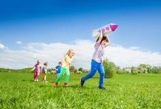 Τρεξίματα αγοριών με το παιχνίδι και τα παιδιά πυραύλων που χαράζουν κατόπιν Στοκ Φωτογραφία