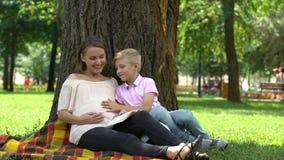 Τρεξίματα αγοριών στο έγκυο βιβλίο ανάγνωσης μητέρων στην υγιούς και ευτυχούς εγκυμοσύνη πάρκων, απόθεμα βίντεο
