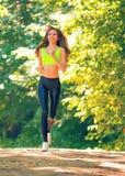 Τρεξίματα αθλητικών κοριτσιών στις ταινίες επίδρασης πάρκων Στοκ Εικόνα