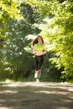 Τρεξίματα αθλητικών κοριτσιών στις ταινίες επίδρασης πάρκων Στοκ Φωτογραφία