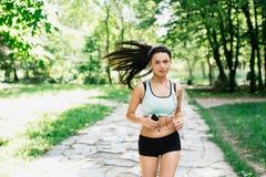 Τρεξίματα αθλητικών κοριτσιών στο πάρκο και άκουσμα τη μουσική Στοκ φωτογραφία με δικαίωμα ελεύθερης χρήσης