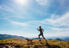 Τρεξίματα ατόμων με το σκυλί λαγωνικών του στην κορυφή βουνών Στοκ φωτογραφία με δικαίωμα ελεύθερης χρήσης