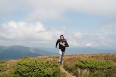 Τρεξίματα ατόμων στο πράσινο λιβάδι στο βουνό στο νεφελώδη ουρανό Στοκ φωτογραφίες με δικαίωμα ελεύθερης χρήσης