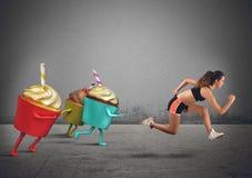 Τρεξίματα γυναικών μακρυά από τα γλυκά Στοκ Εικόνες