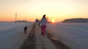 Τρεξίματα γυναικών με ένα σκυλί σε ένα χειμερινό βράδυ στον τρόπο να συναντηθεί το ερυθρό ηλιοβασίλεμα απόθεμα βίντεο