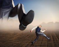 Τρεξίματα επιχειρηματιών από ένα μεγάλο πόδι Στοκ εικόνες με δικαίωμα ελεύθερης χρήσης