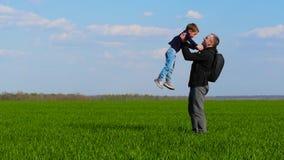 Τρεξίματα ευτυχή παιδιών πέρα από την πράσινη χλόη στα όπλα του πατέρα του, ο οποίος ανατρέφει το παιδί στα όπλα του και τον αγκα φιλμ μικρού μήκους