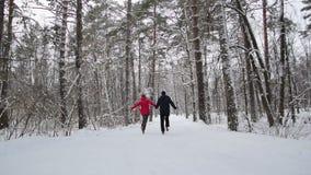 Τρεξίματα ζεύγους στο χειμερινό δάσος σε αργή κίνηση φιλμ μικρού μήκους