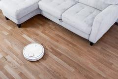 Τρεξίματα ηλεκτρικών σκουπών ρομπότ στο ξύλινο πάτωμα παρκέ Σύγχρονη έξυπνη οικοκυρική τεχνολογίας καθαρισμού στοκ εικόνες