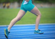 τρεξίματα κοριτσιών γρηγορότερα γύρω από τη διαδρομή κατά τη διάρκεια ενός αθλητικού ανταγωνισμού Στοκ φωτογραφία με δικαίωμα ελεύθερης χρήσης