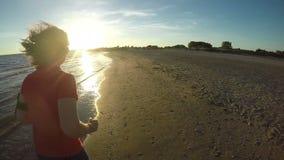 Τρεξίματα κοριτσιών κατά μήκος της παραλίας στο ηλιοβασίλεμα απόθεμα βίντεο