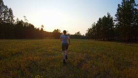 Τρεξίματα κοριτσιών πέρα από τον τομέα στο ηλιοβασίλεμα φιλμ μικρού μήκους