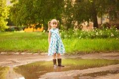 Τρεξίματα κοριτσιών παιδάκι μέσω μιας λακκούβας καλοκαίρι υπαίθριο στοκ εικόνες