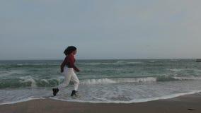 Τρεξίματα κοριτσιών στα κύματα στα παπούτσια απόθεμα βίντεο