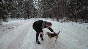 Τρεξίματα λαγωνικών σκυλιών μέσω του χιονιού Χαριτωμένο νέο ζεύγος hipster που έχει τη διασκέδαση στο χειμερινό πάρκο με το σκυλί απόθεμα βίντεο